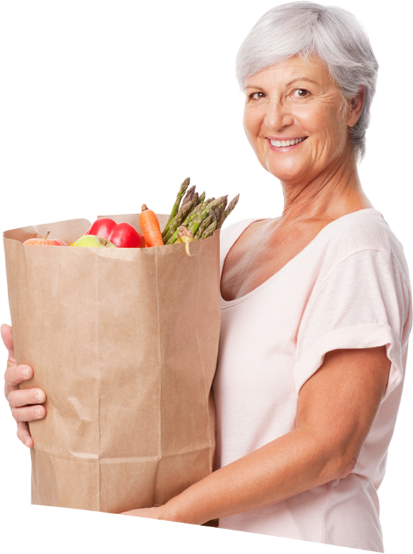 Smiling woman holding a bag of groceries.